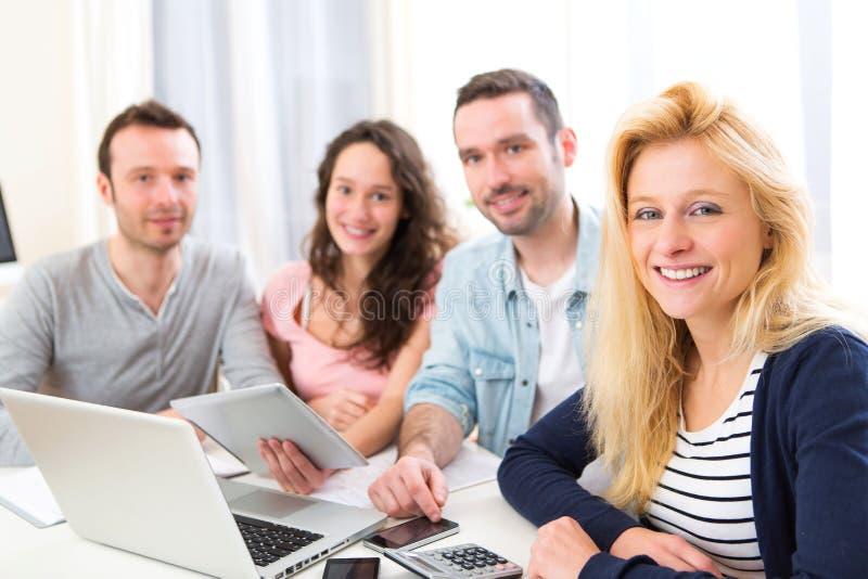 Ομάδα 4 ελκυστικών νέων που εργάζονται σε ένα lap-top στοκ εικόνα