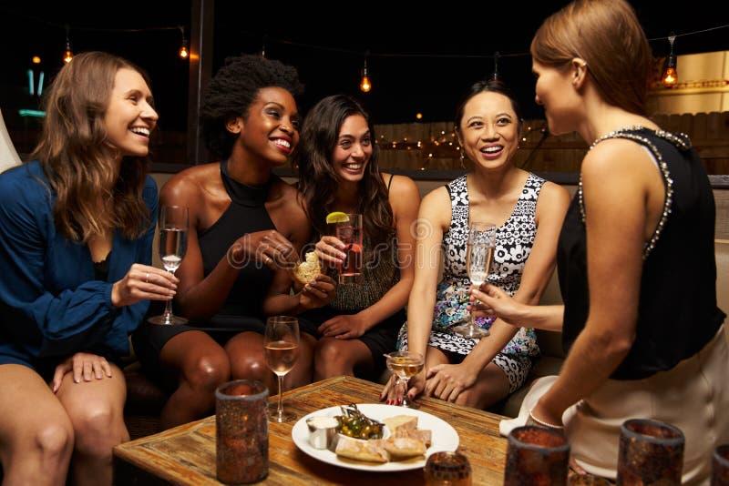 Ομάδα θηλυκών φίλων που απολαμβάνουν τη νύχτα έξω στο φραγμό στεγών στοκ φωτογραφίες