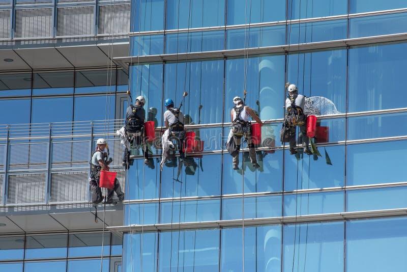 Ομάδα καθαριστών παραθύρων που αναστέλλονται από τα καλώδια στοκ φωτογραφία με δικαίωμα ελεύθερης χρήσης