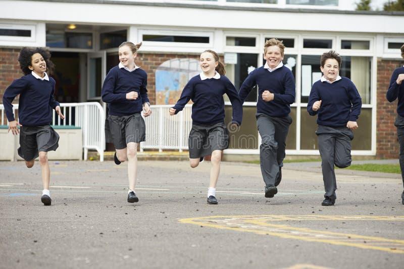 Ομάδα μαθητών δημοτικού σχολείου που τρέχουν στην παιδική χαρά στοκ εικόνες