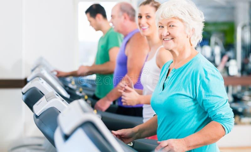 Ομάδα με τους ανώτερους ανθρώπους treadmill στη γυμναστική στοκ φωτογραφίες