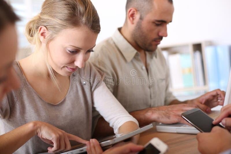 Ομάδα νέων επιχειρηματιών που χρησιμοποιούν τις ηλεκτρονικές συσκευές στοκ εικόνες με δικαίωμα ελεύθερης χρήσης