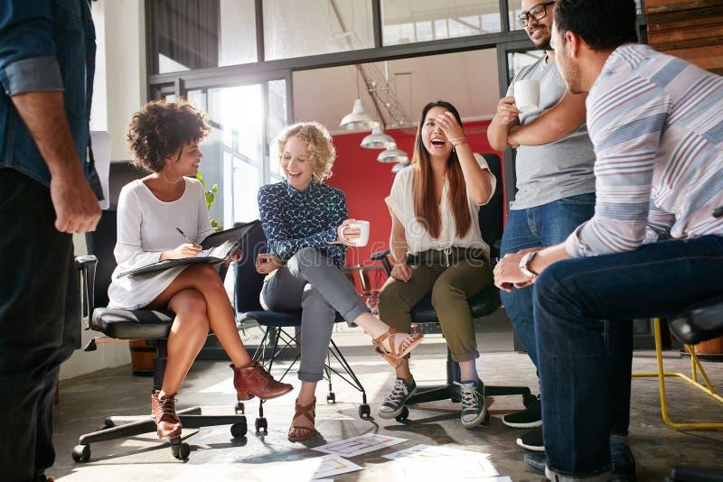 Ομάδα νέων επιχειρησιακών επαγγελματιών που διοργανώνουν μια συνεδρίαση στοκ φωτογραφία