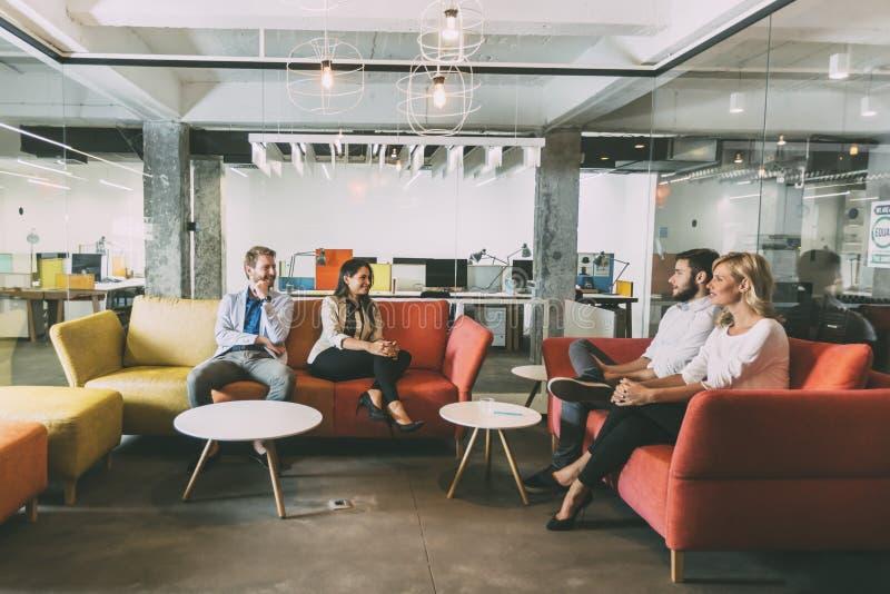 Ομάδα νέων που μιλούν στο σύγχρονο καφέ στοκ εικόνες