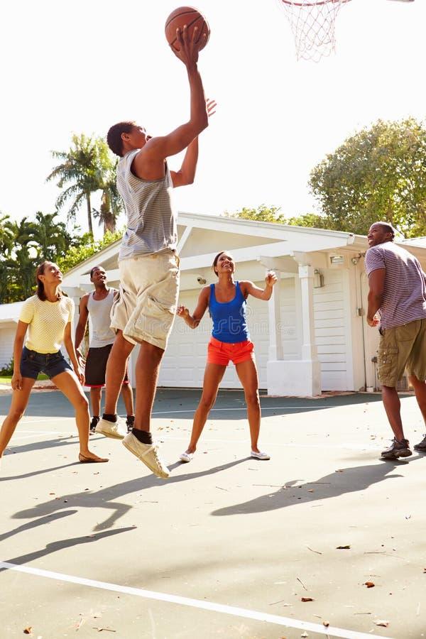 Ομάδα νέων φίλων που παίζουν τον αγώνα καλαθοσφαίρισης στοκ φωτογραφία