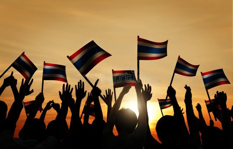 Ομάδα πίσω αναμμένων ανθρώπων που κυματίζουν τη σημαία της Ταϊλάνδης στοκ εικόνα με δικαίωμα ελεύθερης χρήσης