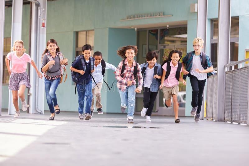 Ομάδα παιδιών δημοτικών σχολείων που τρέχουν σε έναν σχολικό διάδρομο στοκ φωτογραφία