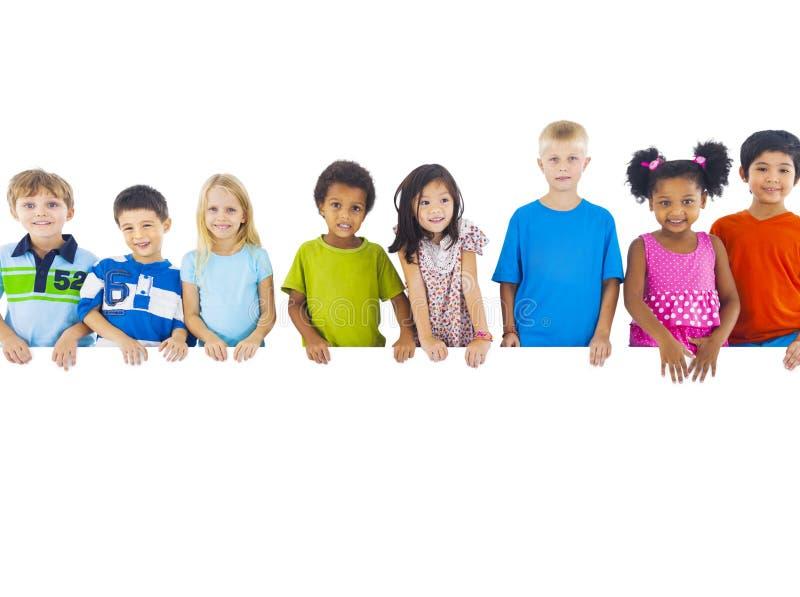 Ομάδα παιδιών που στέκονται πίσω από το έμβλημα στοκ εικόνες με δικαίωμα ελεύθερης χρήσης