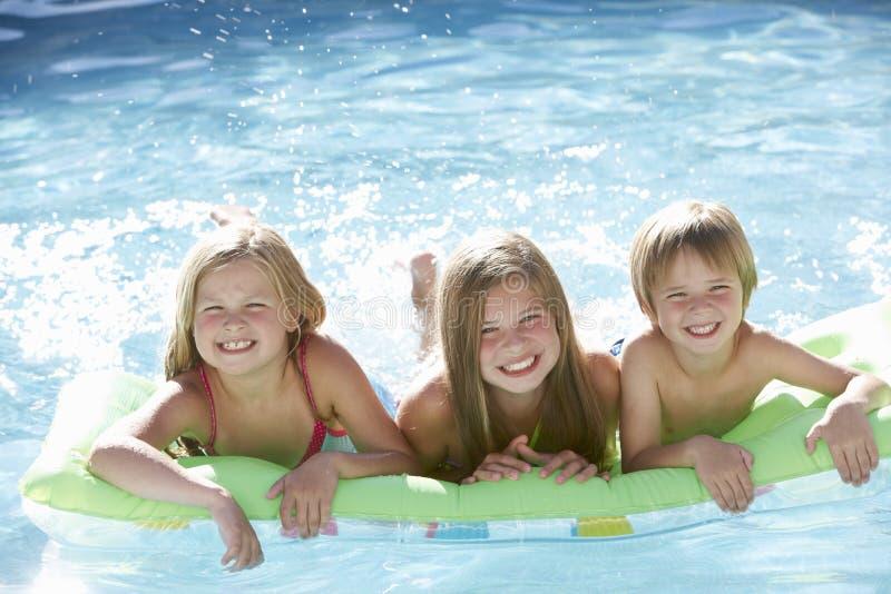 Ομάδα παιδιών που χαλαρώνουν στην πισίνα από κοινού στοκ εικόνες