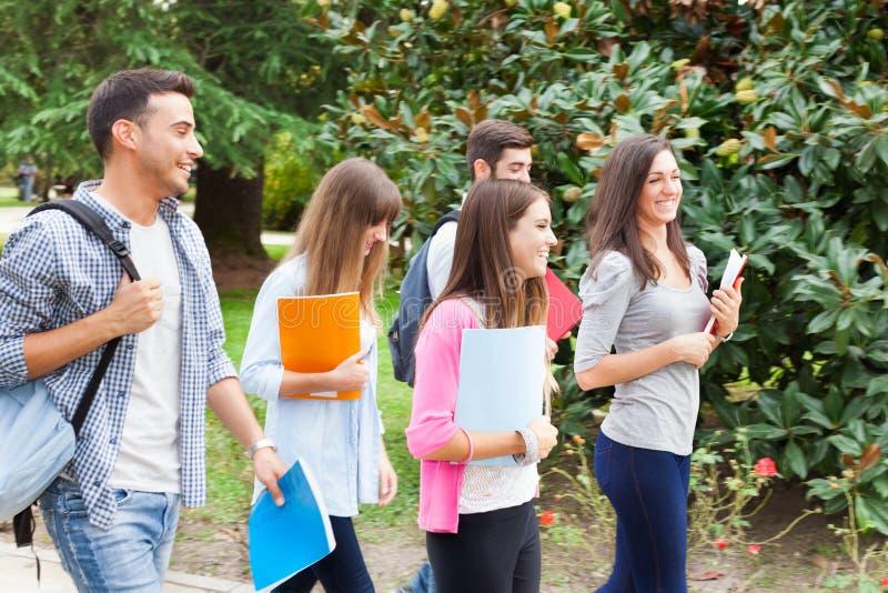 Ομάδα περπατήματος σπουδαστών χαμόγελου υπαίθριου στοκ φωτογραφία