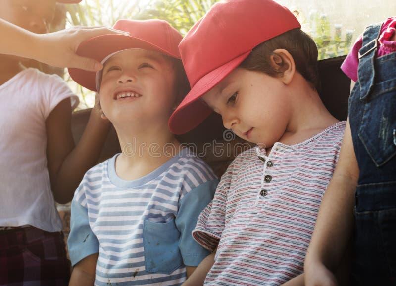 Ομάδα ποικιλομορφίας παιδιών κόκκινη ΚΑΠ που έχουν τη διασκέδαση στοκ εικόνες με δικαίωμα ελεύθερης χρήσης