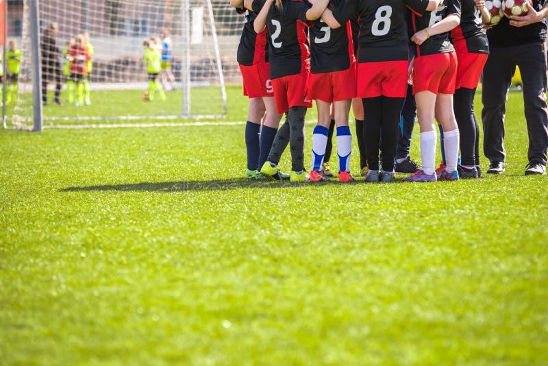 Ομάδα ποδοσφαίρου παιδιών ` s στην πίσσα Κορίτσια στις μαύρες και κόκκινες στολές ποδοσφαίρου στοκ φωτογραφίες