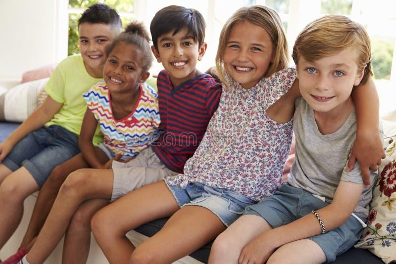 Ομάδα πολυπολιτισμικών παιδιών στο κάθισμα παραθύρων από κοινού στοκ εικόνα