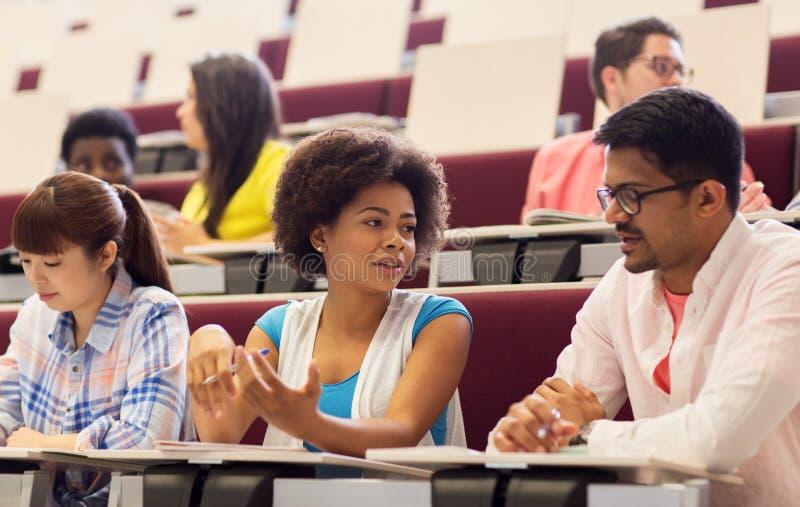 Ομάδα σπουδαστών με τα σημειωματάρια στην αίθουσα διάλεξης στοκ φωτογραφία