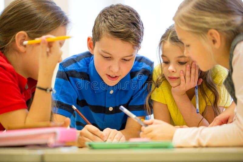 Ομάδα σπουδαστών που μιλούν και που γράφουν στο σχολείο στοκ εικόνες