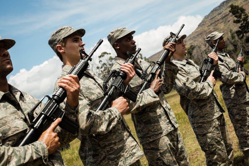 Ομάδα στρατιωτικών στρατιωτών που στέκονται με τα τουφέκια στοκ φωτογραφία