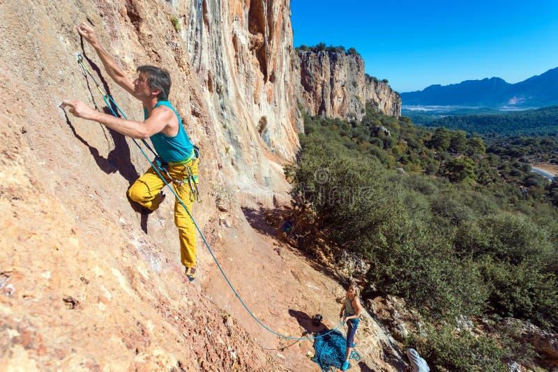 Ομάδα του άνδρα και της γυναίκας ορειβατών που ανέρχονται τον πορτοκαλή φωτεινό δύσκολο τοίχο με το σχοινί και το εργαλείο στοκ εικόνες