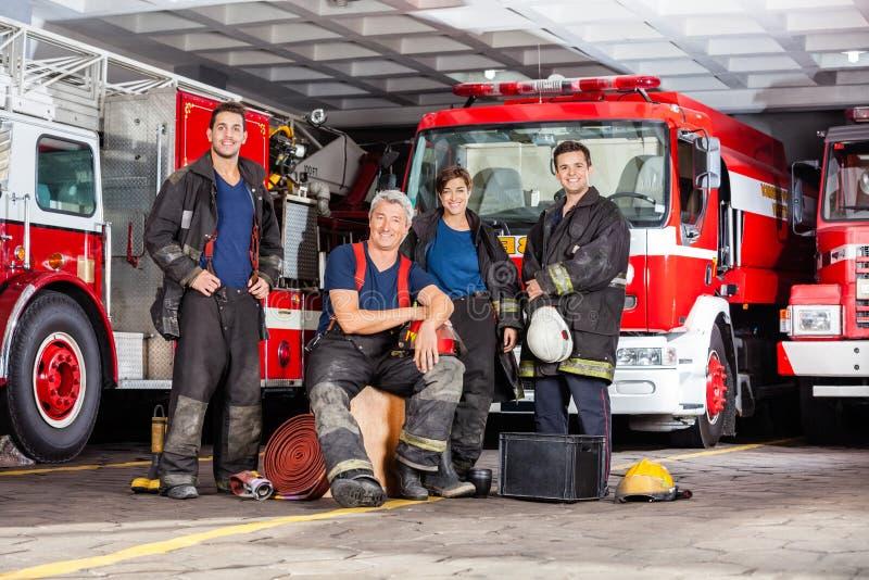 Ομάδα του ευτυχούς πυροσβέστη με τον εξοπλισμό στην πυρκαγιά στοκ φωτογραφίες