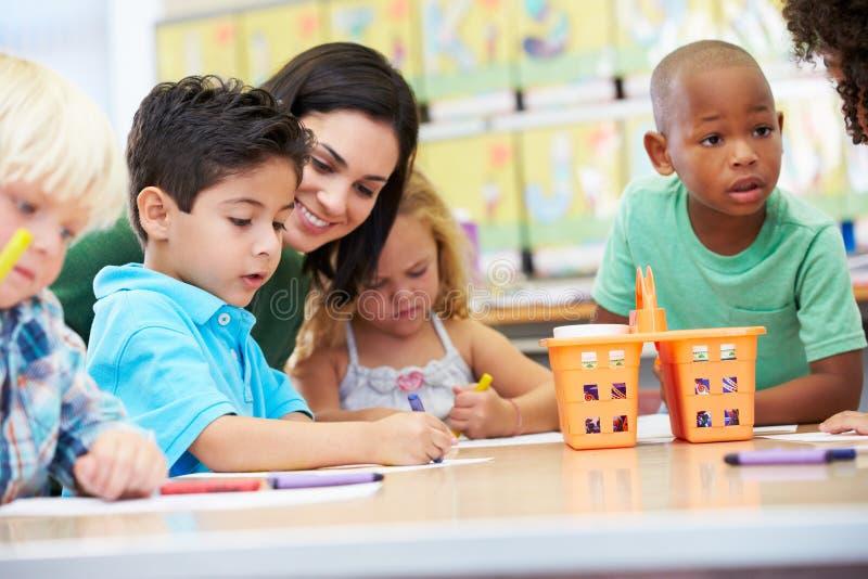 Ομάδα του δημοτικού σχολείου παιδιών ηλικίας στην κατηγορία τέχνης με το δάσκαλο στοκ φωτογραφίες