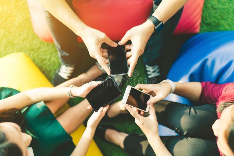 Ομάδα τριών νέων που χρησιμοποιούν smartphones μαζί, σύγχρονης τρόπου ζωής ή έννοιας συσκευών τεχνολογίας επικοινωνιών στοκ εικόνα