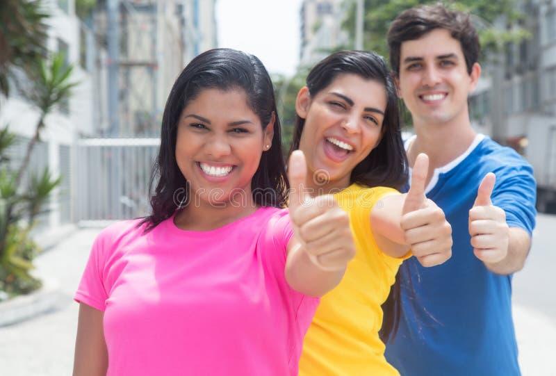Ομάδα τριών νέων στα ζωηρόχρωμα πουκάμισα που στέκονται στη γραμμή και που παρουσιάζουν αντίχειρες στοκ φωτογραφίες με δικαίωμα ελεύθερης χρήσης