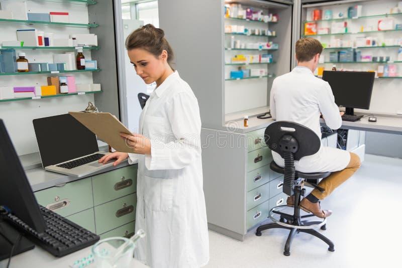 Ομάδα των φαρμακοποιών που εργάζονται στους υπολογιστές στοκ φωτογραφία