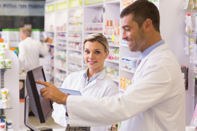 Ομάδα των φαρμακοποιών που χρησιμοποιούν τον υπολογιστή στοκ φωτογραφίες