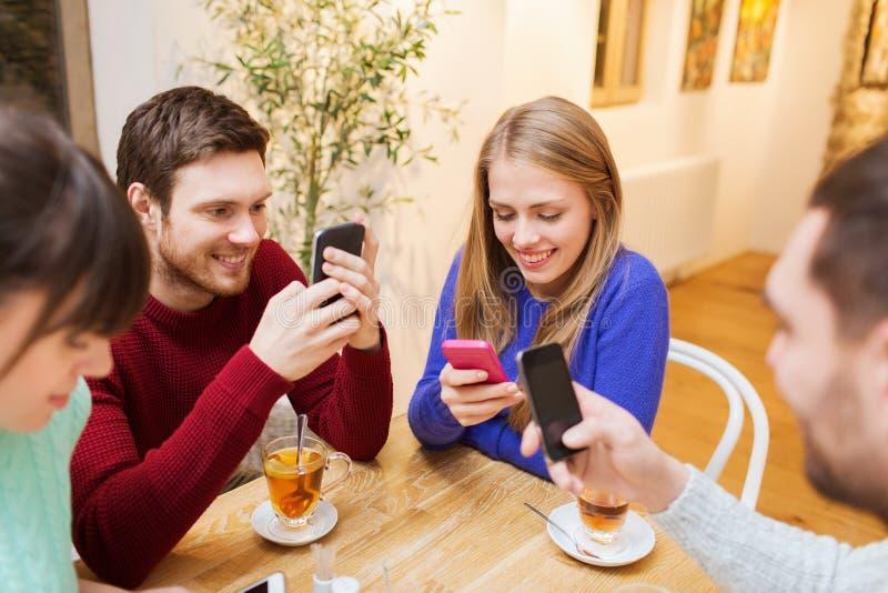 Ομάδα φίλων με τα smartphones που συναντιούνται στον καφέ στοκ φωτογραφίες