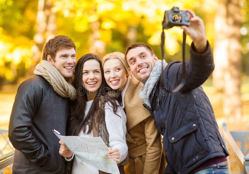 Ομάδα φίλων με τη κάμερα φωτογραφιών στο πάρκο φθινοπώρου στοκ φωτογραφία