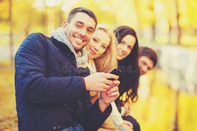 Ομάδα φίλων που έχουν τη διασκέδαση στο πάρκο φθινοπώρου στοκ εικόνες