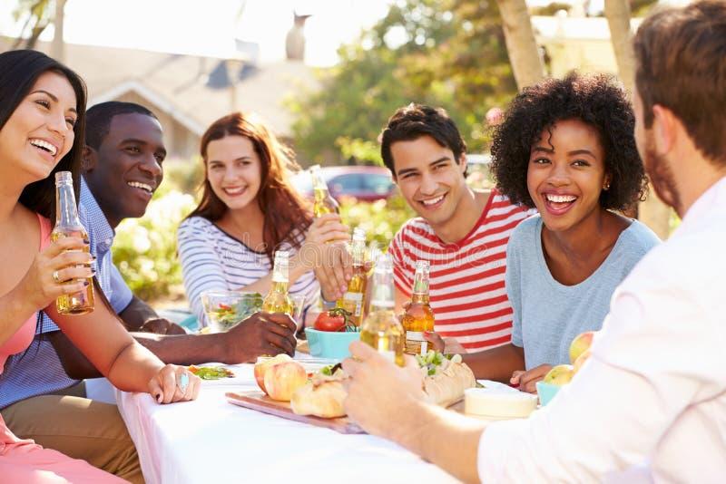Ομάδα φίλων που απολαμβάνουν το γεύμα στο υπαίθριο κόμμα στην πίσω αυλή στοκ εικόνα με δικαίωμα ελεύθερης χρήσης