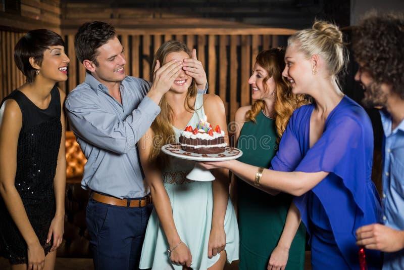 Ομάδα φίλων που εκπλήσσει μια γυναίκα με το κέικ γενεθλίων στοκ φωτογραφία με δικαίωμα ελεύθερης χρήσης