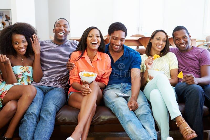 Ομάδα φίλων που κάθονται στον καναπέ που προσέχει τη TV από κοινού στοκ εικόνα με δικαίωμα ελεύθερης χρήσης
