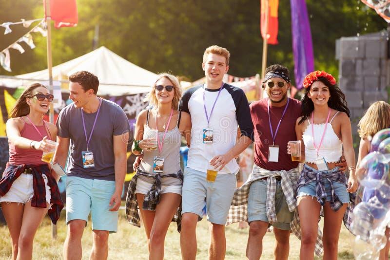 Ομάδα φίλων που περπατούν μέσω μιας περιοχής φεστιβάλ μουσικής στοκ εικόνα με δικαίωμα ελεύθερης χρήσης