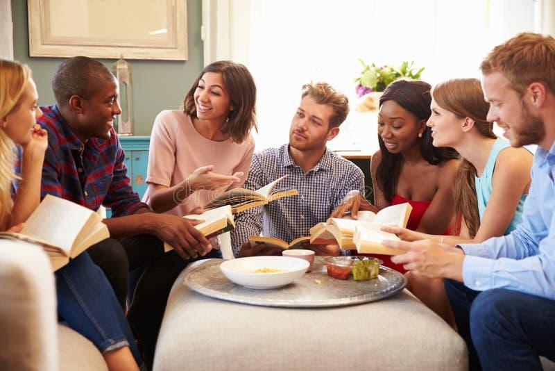Ομάδα φίλων που συμμετέχουν στη λέσχη βιβλίων στο σπίτι στοκ φωτογραφία
