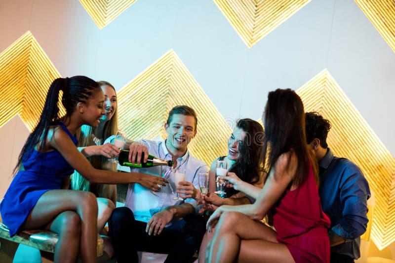Ομάδα χαμογελώντας φίλων που κάθονται στον καναπέ και που έχουν ένα ποτήρι της σαμπάνιας στοκ φωτογραφία με δικαίωμα ελεύθερης χρήσης