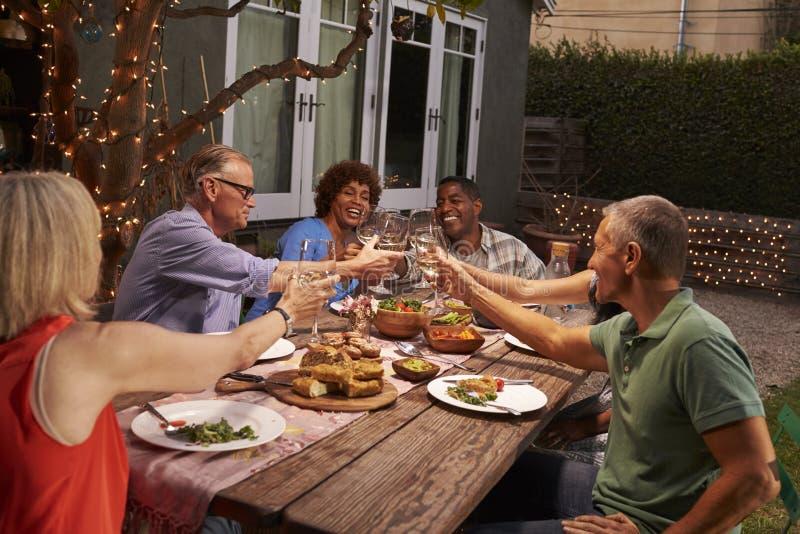 Ομάδα ώριμων φίλων που απολαμβάνουν το υπαίθριο γεύμα στο κατώφλι στοκ εικόνα