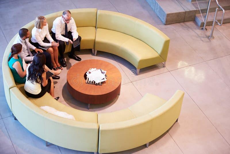 Ομάδα Businesspeople που διοργανώνει τη συνεδρίαση στο λόμπι γραφείων στοκ φωτογραφία με δικαίωμα ελεύθερης χρήσης