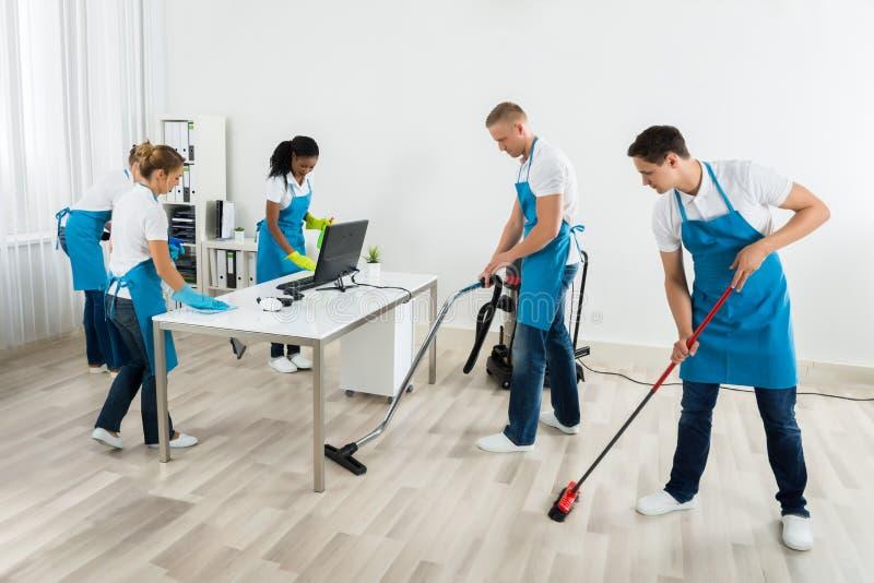 Ομάδα Janitors που καθαρίζουν το γραφείο στοκ εικόνα με δικαίωμα ελεύθερης χρήσης