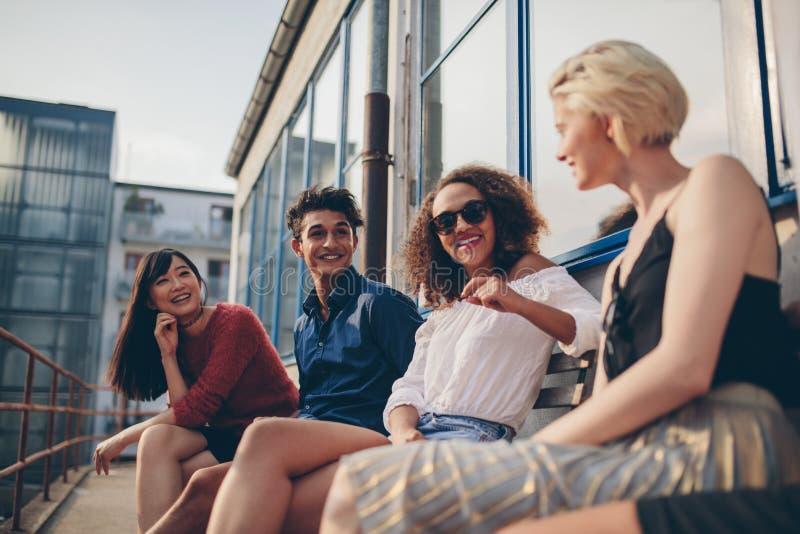 Ομάδα Multiethnic φίλων στο μπαλκόνι και την ομιλία στοκ φωτογραφία