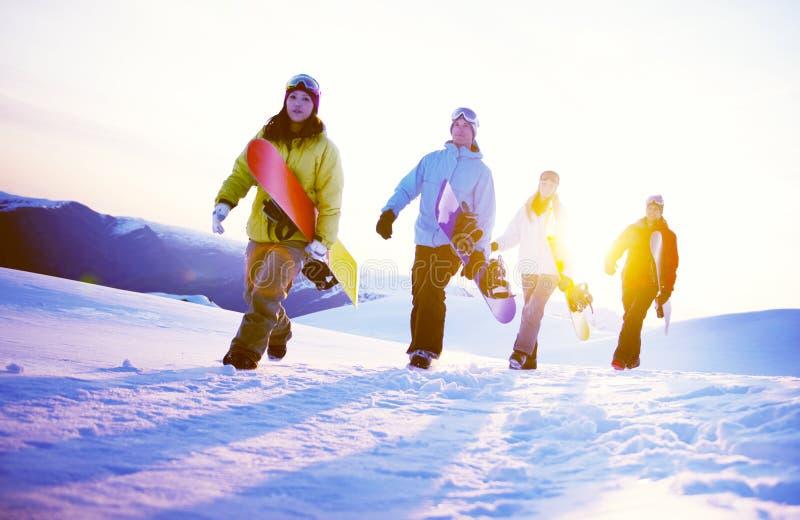 Ομάδα Snowboarders πάνω από την έννοια βουνών στοκ εικόνα