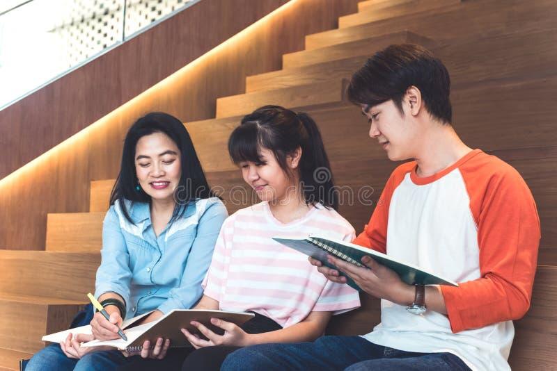 Ομάδες ασιατικών εφηβικών σπουδαστών που μελετούν μαζί στο πανεπιστήμιο στοκ εικόνα