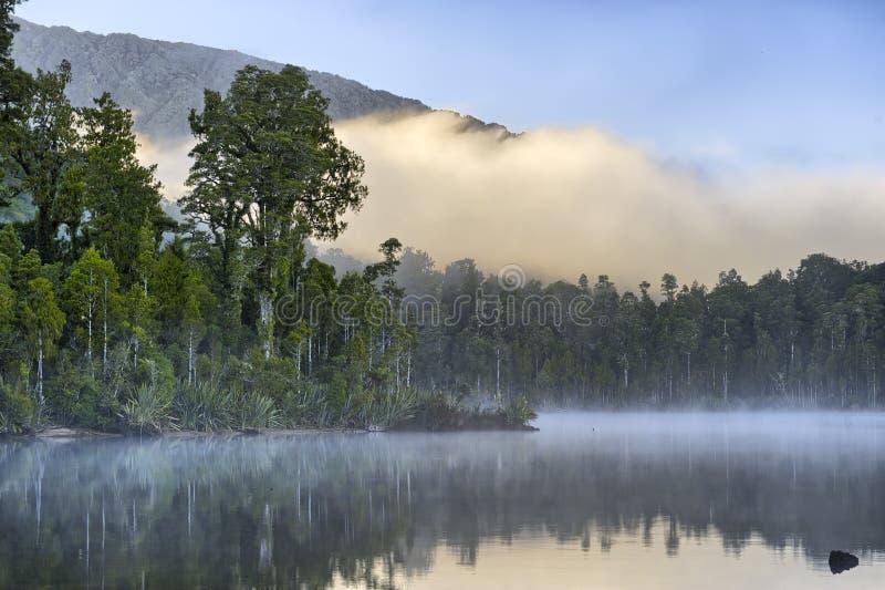 Ομίχλη ξημερωμάτων στη λίμνη Kaniere στοκ εικόνες