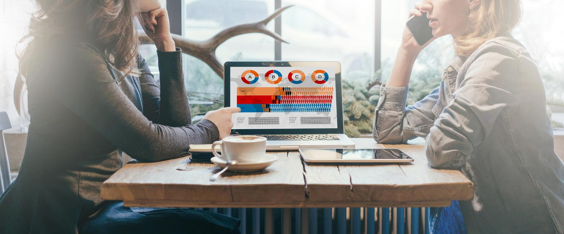 Ομαδική εργασία, δύο νέες επιχειρηματίες που κάθεται πέρα από τον πίνακα μεταξύ τους Στο επιτραπέζιο lap-top, φλυτζάνι καφέ και υ στοκ εικόνα με δικαίωμα ελεύθερης χρήσης