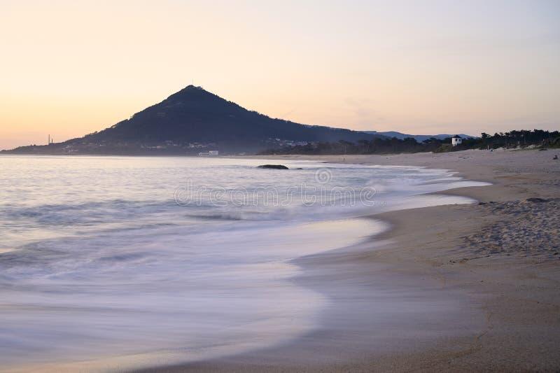 Ομαλά κύματα πέρα από μια αμμώδη παραλία στο ηλιοβασίλεμα με το βουνό στο υπόβαθρο στοκ εικόνες