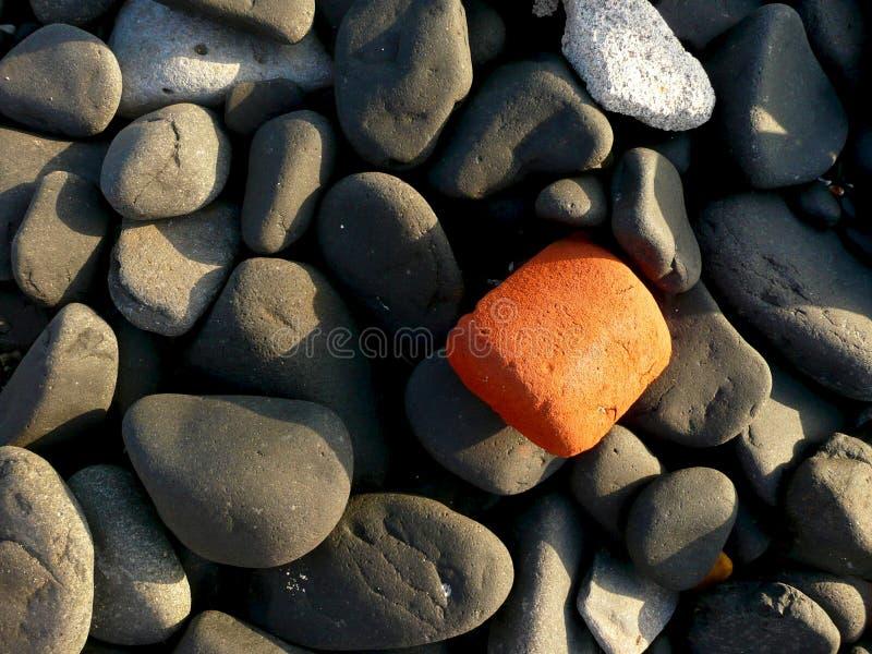Ομαλοί μαύροι βράχοι με έναν πορτοκαλή βράχο στοκ φωτογραφία με δικαίωμα ελεύθερης χρήσης