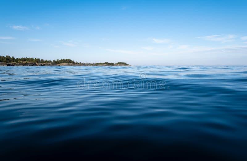 Ομαλό νερό της λίμνης με τα μικρά κύματα, ενάντια σε μια δύσκολη ακτή με τα δέντρα και το μπλε ουρανό, μια θερινή ημέρα Κατώτατη  στοκ φωτογραφίες με δικαίωμα ελεύθερης χρήσης