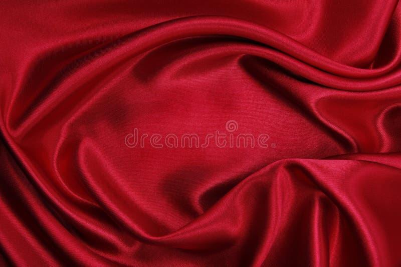 Ομαλή κομψή κόκκινη σύσταση υφασμάτων πολυτέλειας μεταξιού ή σατέν ως abstrac στοκ φωτογραφία με δικαίωμα ελεύθερης χρήσης