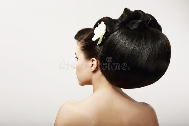 Ομαλή υγιής μαύρη τρίχα με το λουλούδι. Σαλόνι SPA στοκ φωτογραφίες