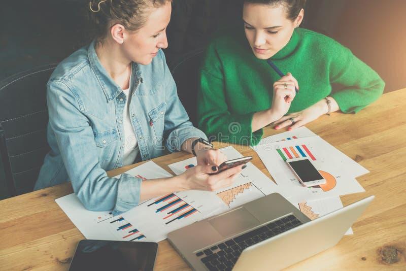 Ομαδική εργασία Δύο νέες επιχειρησιακές γυναίκες που κάθονται στον πίνακα Το κορίτσι παρουσιάζει πληροφορίες συναδέλφων για την ο στοκ εικόνα με δικαίωμα ελεύθερης χρήσης